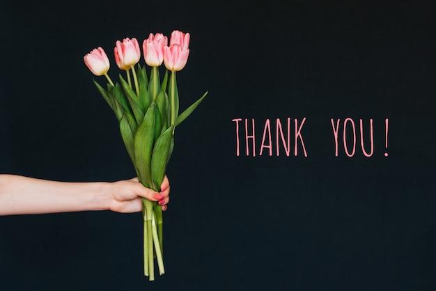 Cartão com a inscrição, obrigado. buquê de flores de tulipa rosa na mão de uma mulher