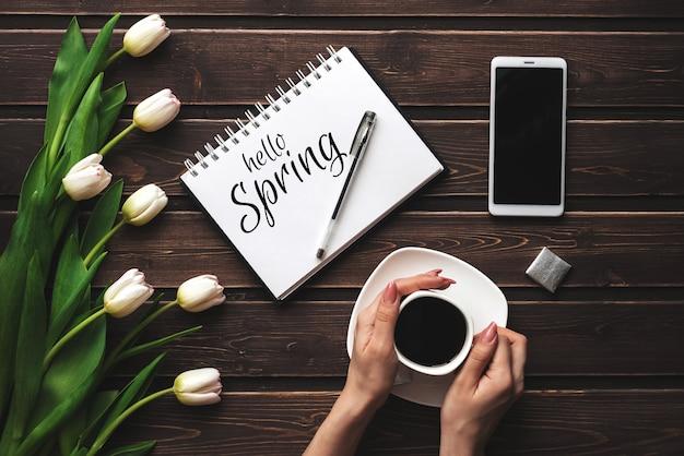 Cartão com a inscrição olá primavera. buquê de tulipas brancas e uma xícara de café com um smartphone