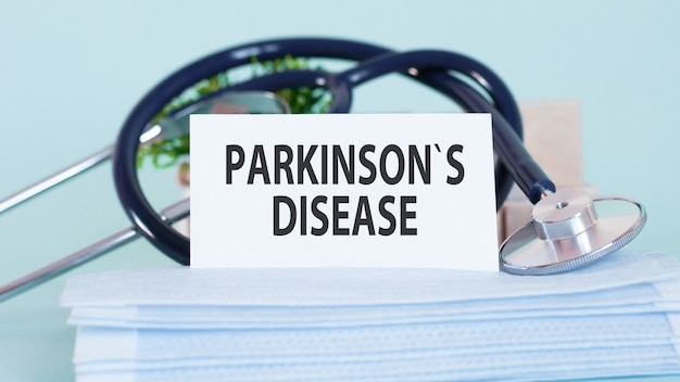 Cartão com as palavras doença de parkinson, estetoscópio, máscaras faciais e flor na mesa na mesa