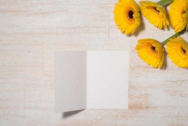 Cartão com flores amarelas sobre fundo de madeira. vista superior com espaço de cópia
