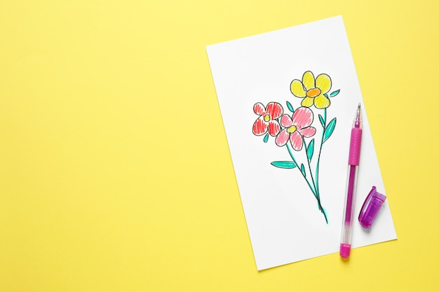 Cartão com flores desenhadas e caneta em fundo amarelo, vista superior. feliz dia das mães