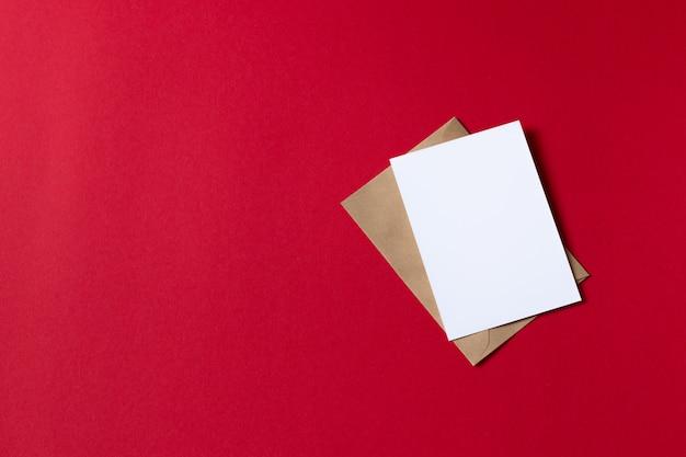 Cartão com modelo de envelope de papel marrom kraft simulado acima sobre fundo vermelho