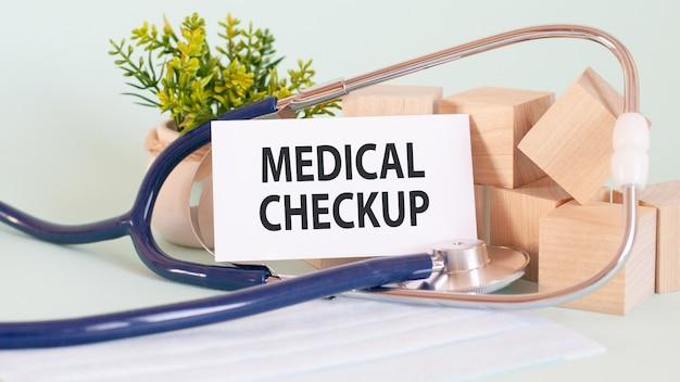 Cartão com palavras checkup médico, stetoscop, blocos de madeira e flores na mesa, conceito médico e de saúde