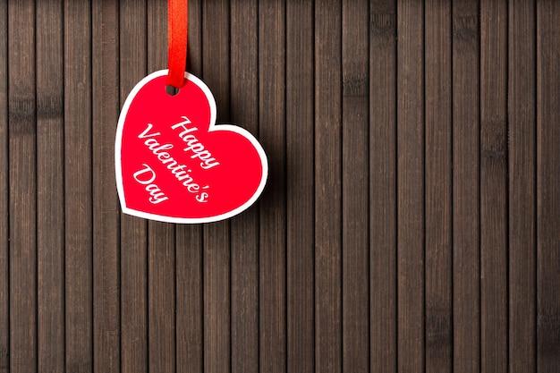 Cartão com palavras de feliz dia dos namorados fixadas em uma corda no fundo de madeira.