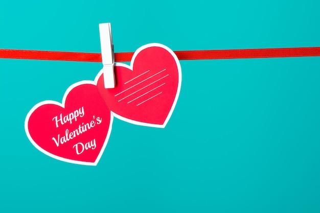 Cartão com palavras de feliz dia dos namorados fixadas em uma corda no fundo turquesa.