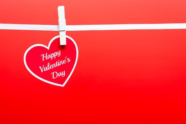 Cartão com palavras de feliz dia dos namorados fixadas em uma corda sobre o fundo vermelho.