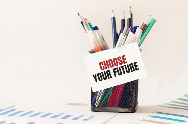 Cartão com texto escolha o seu futuro na caixa de canetas no escritório. diagrama