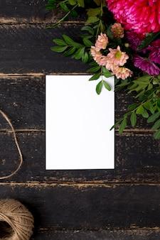 Cartão com um buquê de flores em uma madeira escura vintage