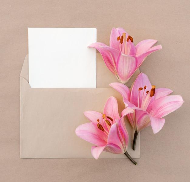 Cartão com um buquê de lírios rosa em um envelope com espaço de cópia para o design