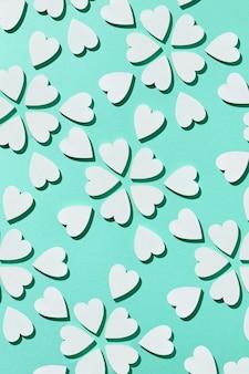 Cartão comemorativo do dia dos namorados com flores criativas padrão feito à mão de pequenos corações de gesso em uma parede turquesa pastel com sombras duras, copie o espaço. postura plana.
