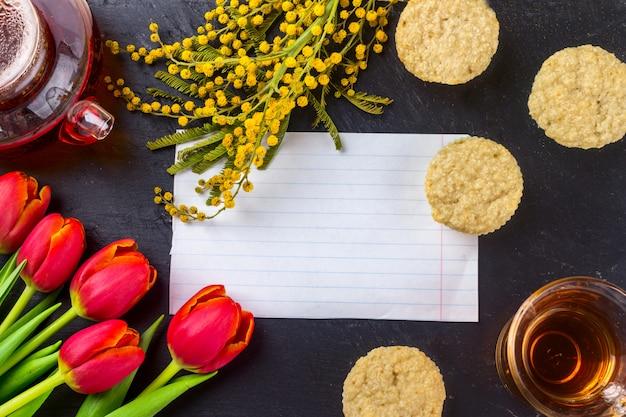 Cartão da mola com tulipas, mimosa, chá e queques no fundo de pedra preto da placa.