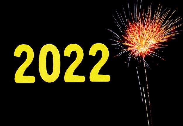 Cartão de ano novo para 2022 com dígitos de ouro em um fundo de fogo de artifício.