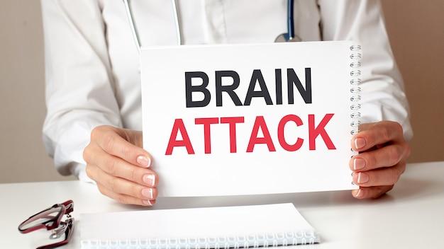 Cartão de ataque cerebral nas mãos do médico. o médico entrega uma folha de papel com o texto ataque cérebro, conceito médico.