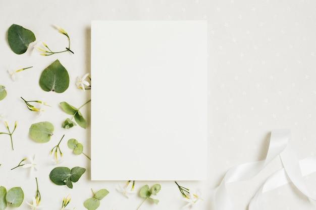 Cartão de casamento branco em branco com flores de jasminum auriculatum e fita em pano de fundo branco