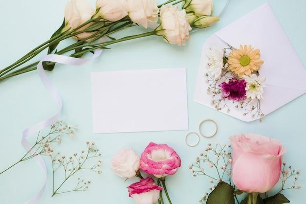 Cartão de casamento em branco com dois anéis e decoração de flores sobre fundo azul