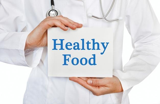 Cartão de comida saudável nas mãos do médico