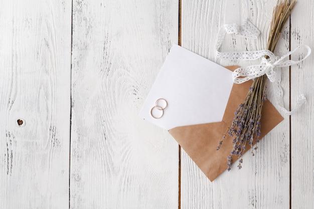Cartão de convite de casamento com envelope na mesa de madeira