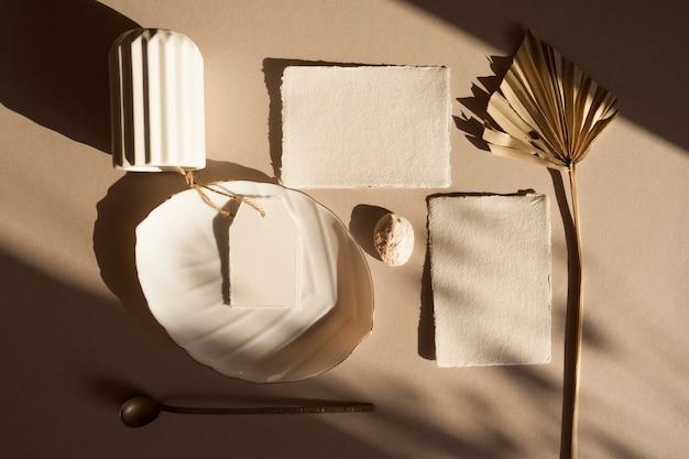 Cartão de convite de saudação de casamento branco em branco com tag, folhas de palmeira tropical seca, placa de vaso, na mesa texturizada de madeira modelo moderno elegante. vista superior plana leiga