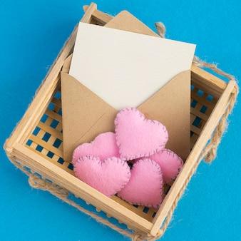 Cartão de convite vazio. velho envelope na cesta de vime de madeira com corações rosa de pelúcia no azul