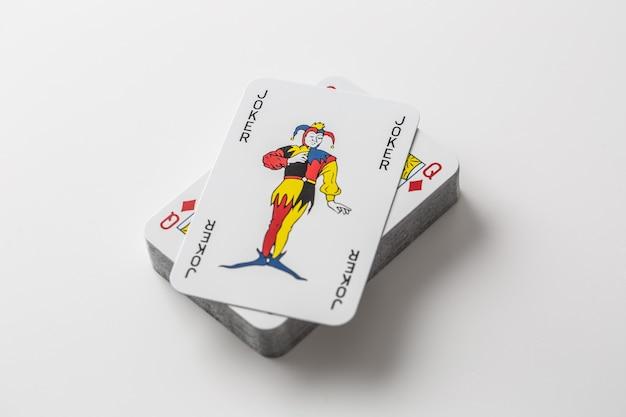 Cartão de coringa no topo da pilha de cartas de jogar em um fundo branco isolado.