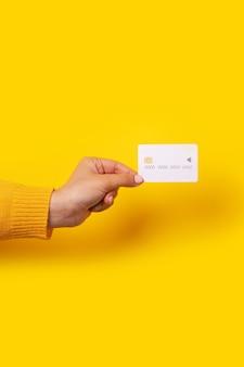 Cartão de crédito branco em branco na mão, cartão com chip eletrônico sobre fundo amarelo