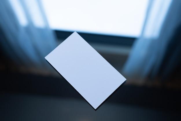 Cartão de crédito branco em branco ou cartão de nome na mesa, simulação.