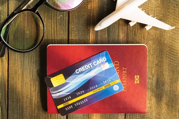 Cartão de crédito colocado no passaporte na mesa de madeira, conceito de preparação para viajar