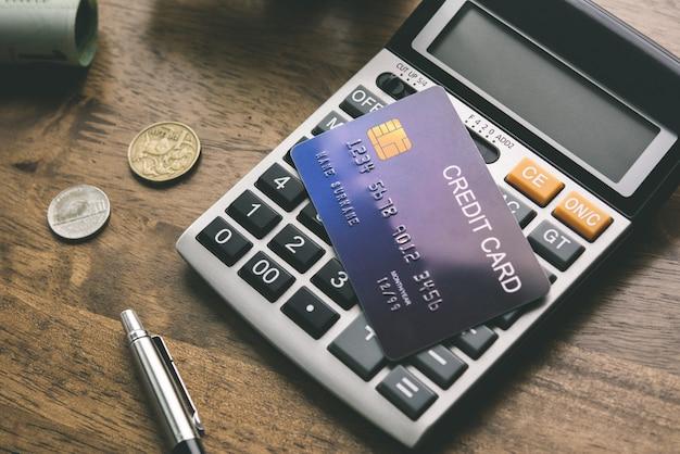 Cartão de crédito com calculadora e algum dinheiro na mesa
