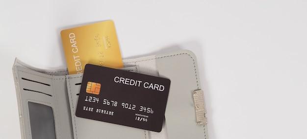 Cartão de crédito cor preta e dourada com carteira cinza isolada no fundo branco.