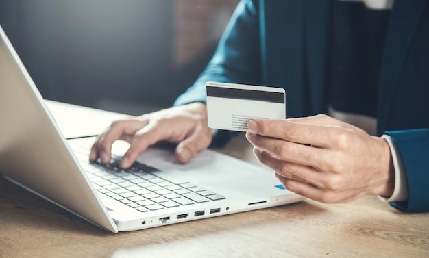 Cartão de crédito da mão do homem e computador na mesa