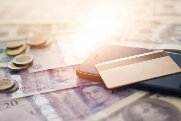 Cartão de crédito de cor dourada e telefone inteligente móvel em notas e moedas