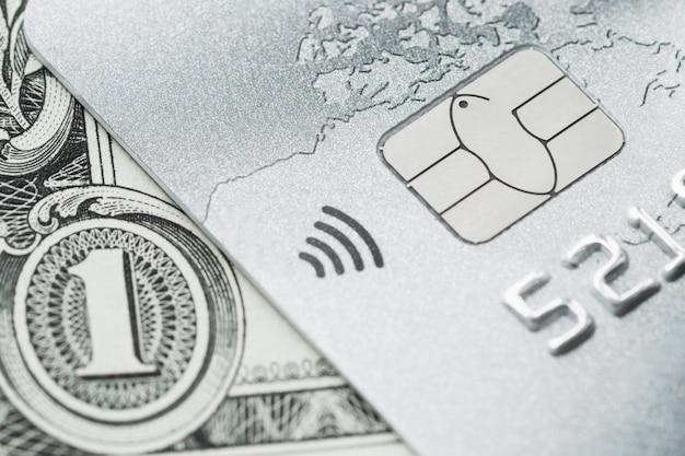 Cartão de crédito de platina no fundo da nota de dólar.