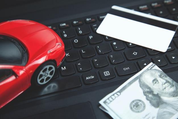 Cartão de crédito, dólar e carro de brinquedo vermelho no teclado do laptop.