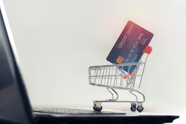 Cartão de crédito e carrinho de compras em um laptop