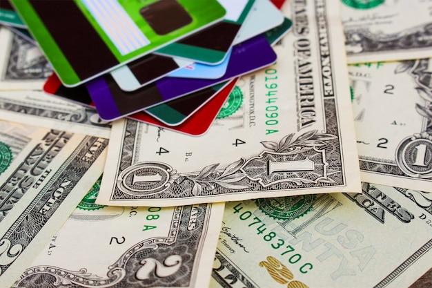 Cartão de crédito e dólares em fundo de madeira.