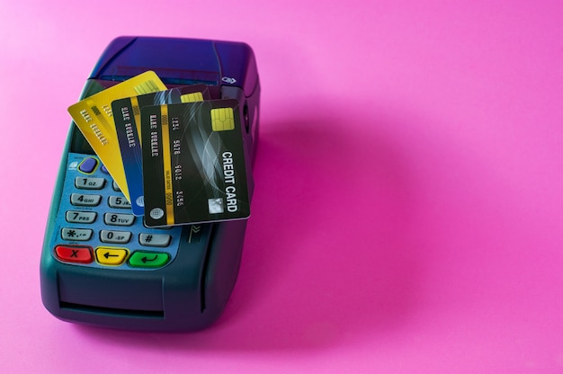 Cartão de crédito e scanner de cartão de crédito em um fundo rosa