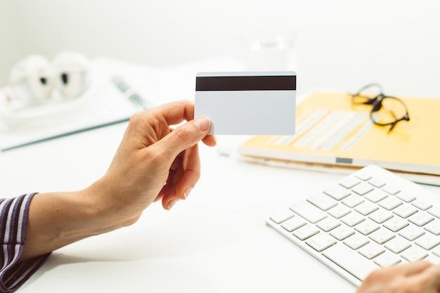 Cartão de crédito em branco branco na mão no teclado.