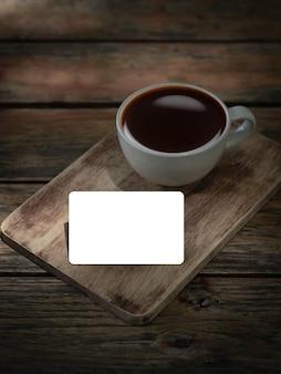 Cartão de crédito em branco com uma xícara de café na mesa de madeira