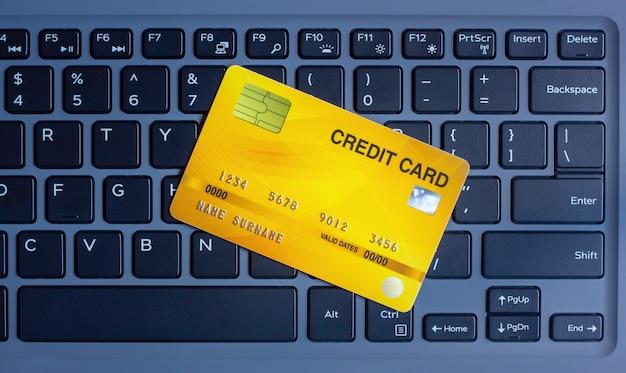 Cartão de crédito em teclado moderno conceito de compras on-line na internet usando um laptop e pagamento de contas