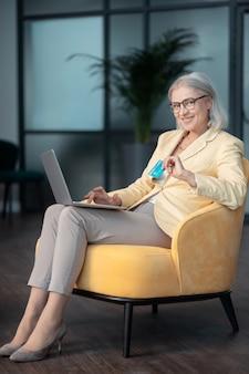 Cartão de crédito. mulher sorridente de cabelos grisalhos em roupas elegantes, sentada em uma confortável poltrona amarela com um laptop e um cartão de débito