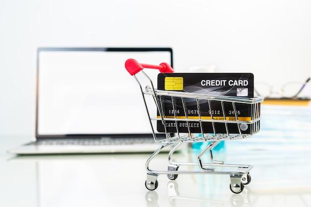 Cartão de crédito na frente do carrinho de compras da tela do laptop com frasco de gel de álcool