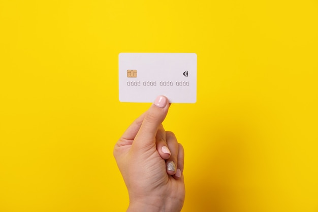 Cartão de crédito na mão, cartão com chip eletrônico sobre fundo amarelo