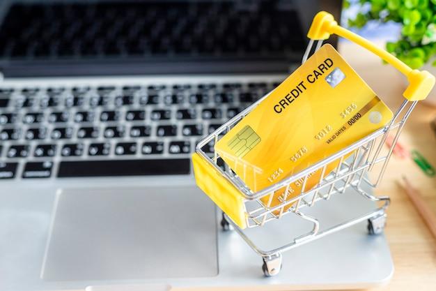 Cartão de crédito no carrinho de compras com laptop, notebook, árvore de vaso de flores sobre fundo de madeira, mesa de escritório on-line bancário vista superior.