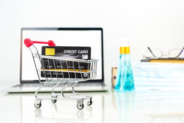 Cartão de crédito no carrinho de compras na frente da tela do laptop com garrafa de álcool gel, conceito de trabalho em casa