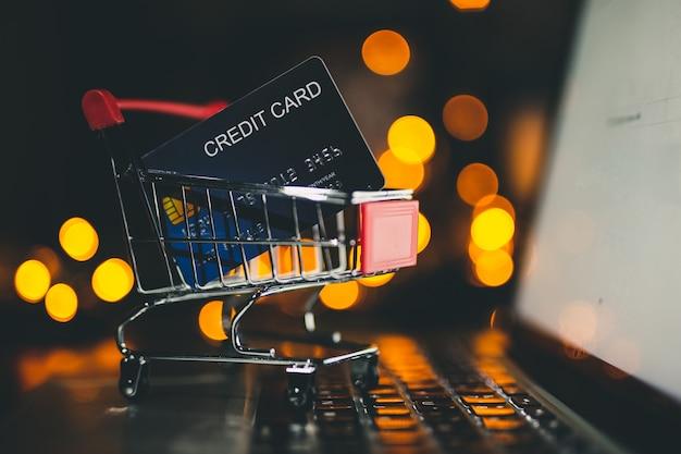 Cartão de crédito no carrinho pequeno, conceito on-line de compras.