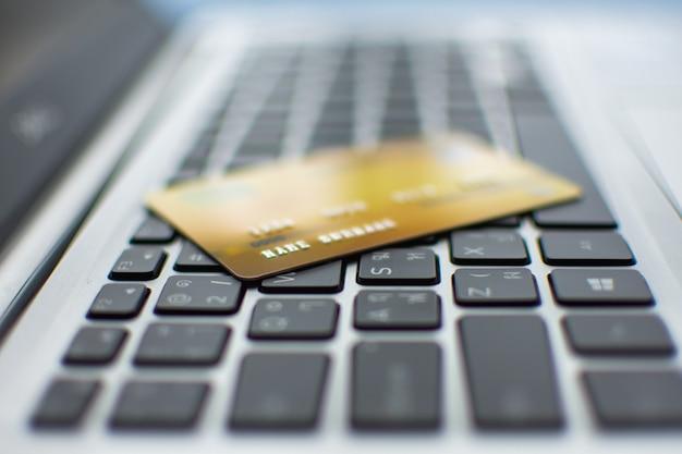 Cartão de crédito no computador, comprando o conceito on-line.