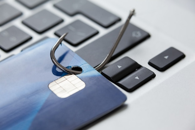 Cartão de crédito no gancho de pesca no laptop