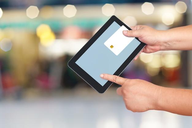 Cartão de crédito ou cartão de débito e tablet na mão
