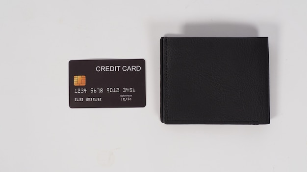 Cartão de crédito preto e carteira preta sobre fundo branco.