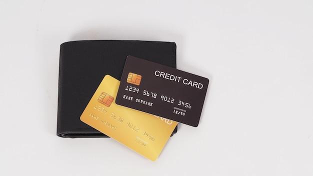 Cartão de crédito preto e cor de ouro na carteira preta isolada no fundo branco.